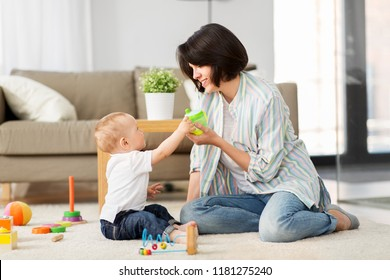 family, child and motherhood concept - happy mother with little baby son playing developmental toys and sippy cup at home