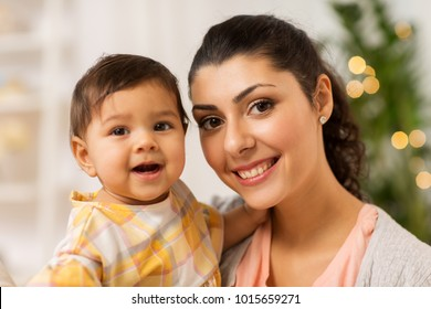 family, child and motherhood concept - portrait of happy smiling mother with little baby daughter