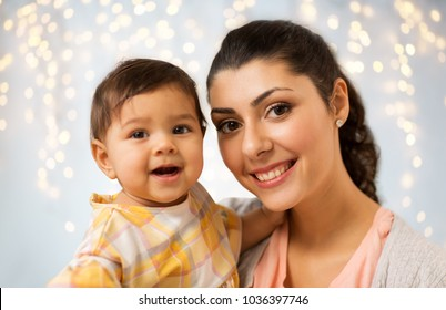 family, child and motherhood concept - portrait of happy smiling mother with little baby daughter over holidays lights background