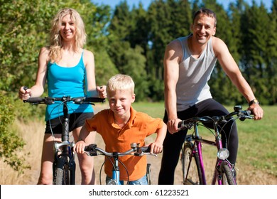 Family with child on their bikes on a summer day in sport outfit, they are exercising