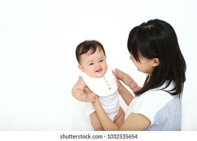 family, child and parenthood concept - happy smiling young mother with little girl baby