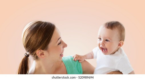 family, child and parenthood concept - happy smiling young mother with little baby over beige background