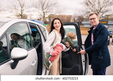 The family with a child standing near the car. Buying a car. Going to traveling