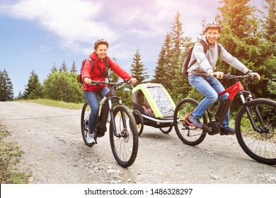 Family With Child In Trailer Riding Mountain Bikes In Alps