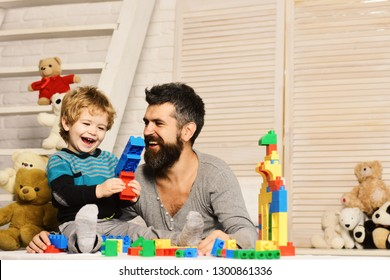 Family and childhood concept. Boy and bearded man play together on wooden wall background. Father and son with cheerful faces create colorful toy gun with bricks. Dad and kid build of plastic blocks