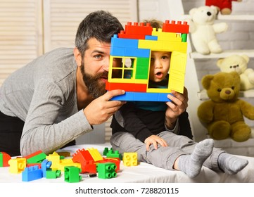 Family and childhood concept. Boy and bearded man play together on nursery background. Dad and kid hide behind plastic blocks wall. Father and son make grimaces looking through window of toy house