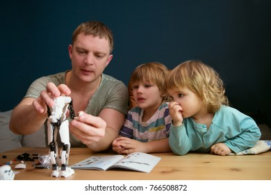 Family and childhood concept. Father and his little children play together  plastic blocks and makes robot.