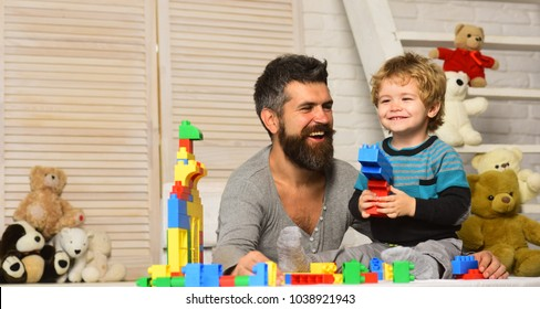 Family and childhood concept. Father and son with happy faces create colorful constructions with bricks. Man and boy play together. Dad and kid with toys on wooden background build of plastic blocks