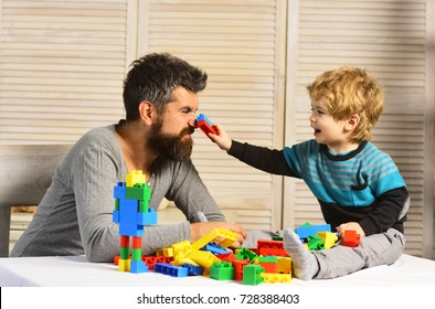 Family and childhood concept. Man with beard and boy play together on wooden wall background. Dad and kid build of plastic blocks. Father and son with happy faces create colorful robot with toy bricks