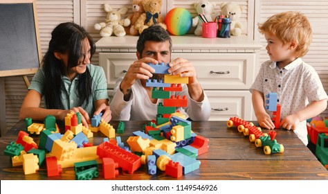 Family and childhood concept. Young family spends time in playroom. Mom, dad and boy with toys on room background build out of plastic blocks. Parents and son with busy faces make brick constructions.