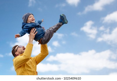 family, childhood and fatherhood concept - happy father and little son playing and having fun outdoors over blue sky and clouds background
