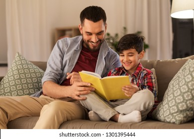 family, childhood, fatherhood, leisure and people concept - happy smiling father and little son reading book on sofa at home