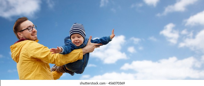 family, childhood, fatherhood, leisure and people concept - happy father and little son playing and having fun over blue sky and clouds background