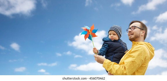family, childhood, fatherhood, leisure and people concept - happy father and little son with pinwheel toy over blue sky and clouds background