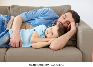 family, childhood, fatherhood, leisure and people concept - portrait of happy father and little son sleeping on sofa at home