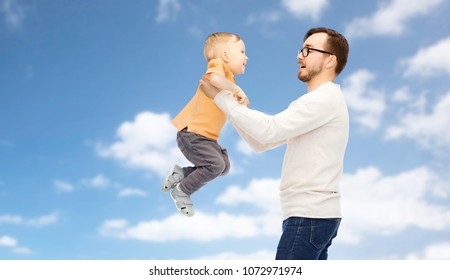 family, childhood, fatherhood and people concept - happy father and little son playing and having fun over blue sky and clouds background