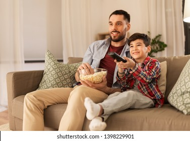 family, childhood, fatherhood, technology and people concept - happy father and little son with popcorn and remote control watching tv at home in evening