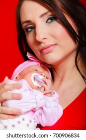 Family, childhood and parenthood concept. Little newborn baby sleeping on mother chest. Red background