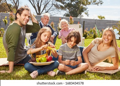Family with children and grandparents is having a picnic in the summer garden