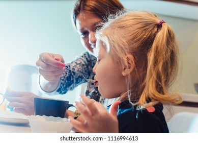 family, children, hapiness and people concept. Happy family with children at the table drinking tea and eating pancakes with various fillings. daughter with a cup close up view