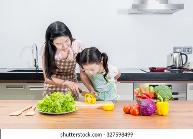 family, children and happy people concept - Asian mother and kid daughter cooking in the kitchen at home. Looking happy family