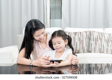 family, children and happy people concept - Asian Mother and daughter playing with digital tablet at home