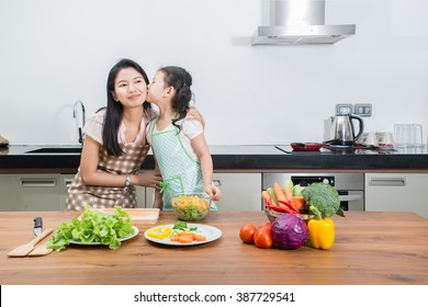 family, children and happy people concept - Asian mother and kid daughter cooking in the kitchen at home.