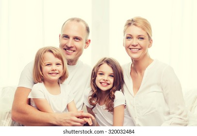 family, children and home concept - smiling parents and two little girls at home
