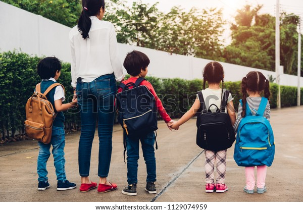 Family children kids son boy and girl daughter kindergarten have backpack walking going to school holding hand mother or mom, back to school concept