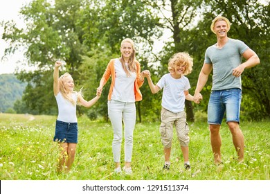 Family and children laugh and dance together happily in the garden