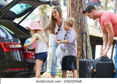 Family and children load car with luggage before traveling on summer vacation