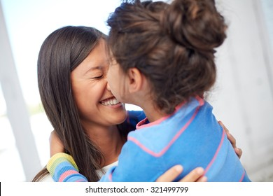 family, children, love and happy people concept - happy little girl hugging mother and kissing her on nose at home