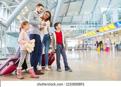 Family and children with luggage in airport terminal fly together on vacation