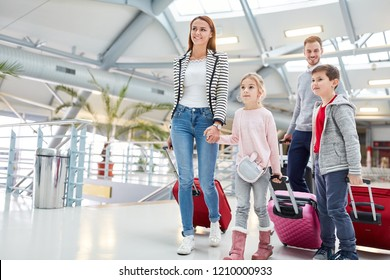 Family with children on the way to the connecting flight at the stopover in the airport terminal
