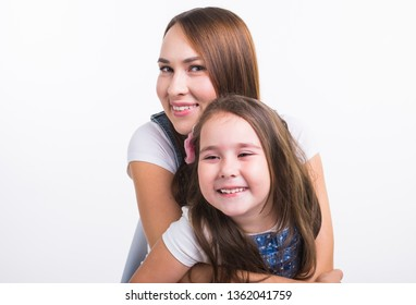 Family, children and parenthood concept - Young woman with her little cute child on white background. Mom with daughter