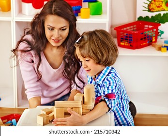 Family with children playing bricks.