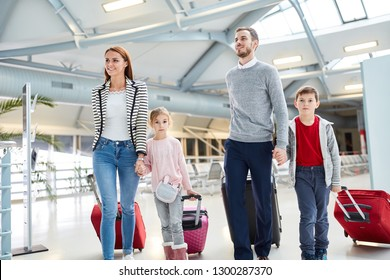 Family with children and suitcases in airport terminal flies together on vacation