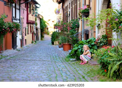 Family with children traveling in Alsace region, France. Little girl enjoying cosy streets of medieval city Eguisheim.