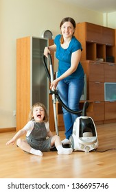 Family chores with vacuum cleaner on parquet