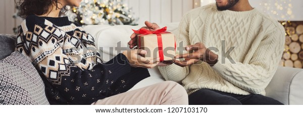 Family Christmas celebration. African-american couple in love exchanging Xmas gifts, copy space