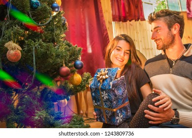 family christmas happy couple opening xmas gifts under home christmas tree.  private christmas party with man and woman concept.