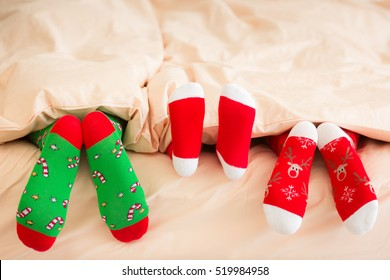 Family in Christmas socks lying on bed. Mother, father and baby having fun together. People relaxing at home. Winter holiday Xmas and New Year concept