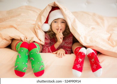 Family in Christmas socks lying on bed. Mother, father and child having fun together. People relaxing at home. Winter holiday Xmas and New Year concept