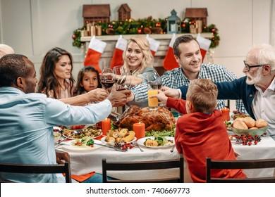 family clinking glasses while having christmas dinner