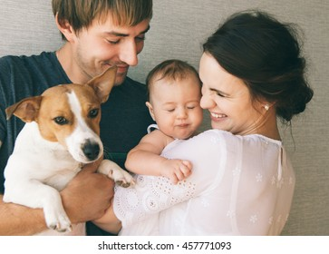 Family close-up portrait: parents, little cute baby girl and their pet - jack russel terrier dog.
