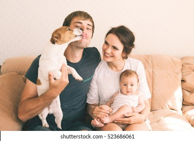Family close-up portrait - parents, their little cute baby girl and their pet - jack russel terrier dog