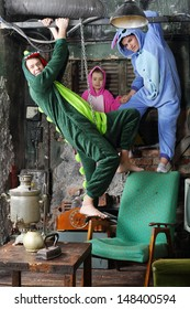 Family in colorful costumes of dragons play in very old room with table and samovar.