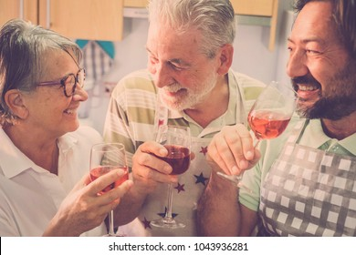 family composed by father and mother senior adult aged and son middle age 45 years old. together having fun at home in the kitchen drinking some red wine for cocktail time. everybody smiling and fun.
