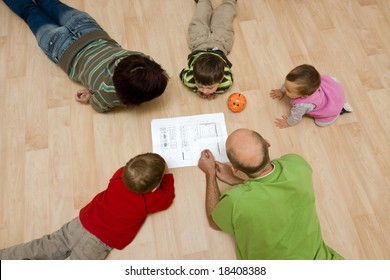 A family comprising parents and their 3 kids lying on the floor and checking the design of their new house on the paper.