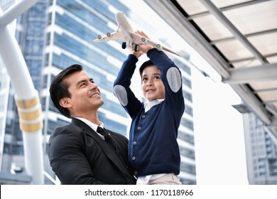Family concept. Dad and son are playing fun toys. A businessman is carrying his son inside the city.
